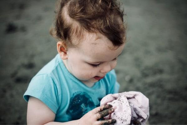 Un enfant, qui a les mains sales, regarde son doudou, comparaison avec l'odorat du chien.